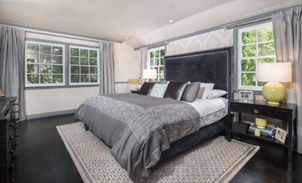 Phòng ngủ sang trọng với rất nhiều cửa sổ mở ra không gian vườn cây tươi xanh.