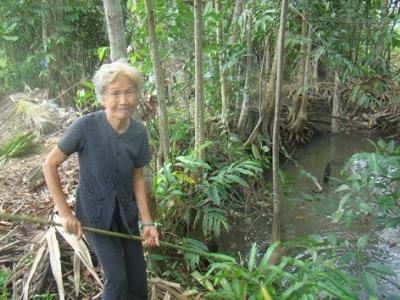 Bà Nguyễn Thị Nay bên đìa tôm đã bỏ hoang từ nhiều năm nay do nước rạch Bà Chèo bị ô nhiễm nặng