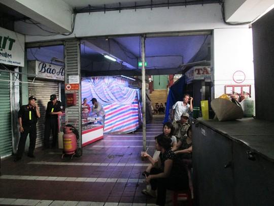 Các tiểu thương ngồi ở lối vào khu chợ phản đối việc đập bỏ khu chợ Đầm tròn để xây đài phun nước