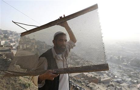 Ảnh một cư dân sinh sống trên sườn đồi Maina Jamal đang mang theo tấm lưới xuống trung tâm thành phố Kabul