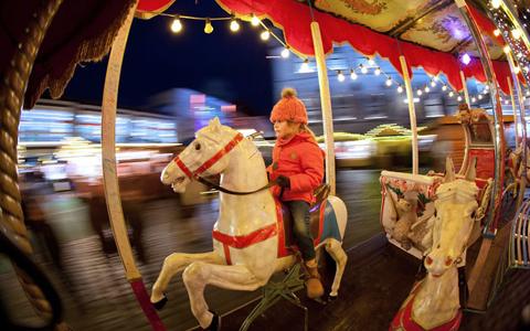 Một em nhỏ cưỡi ngựa gỗ trong lòng hội chợ lung linh và ấm áp. Ảnh: EPA